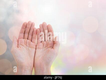 Digital composite of Hands open gentle with sparkling light bokeh background - Stock Photo