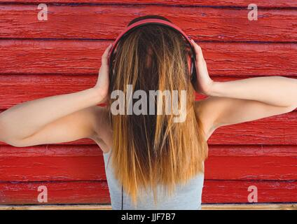 Digital composite of hipster woman listening music with red wood background - Stock Photo