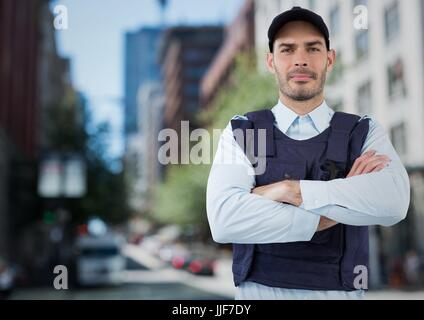 Digital composite of Security guard with arms folded against blurry street - Stock Photo