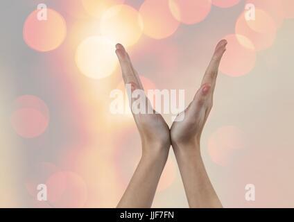 Digital composite of Hands in V Shape with sparkling light bokeh background - Stock Photo
