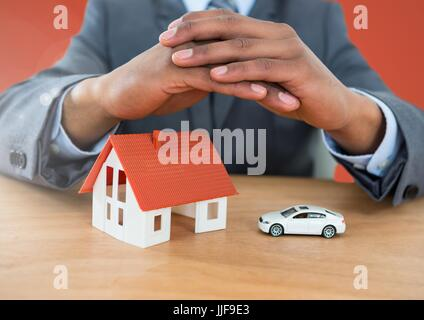 Digital composite of Models hands protective over house and car - Stock Photo