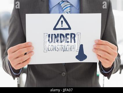 Digital composite of Navy construction doodle on card held by business man mid section - Stock Photo