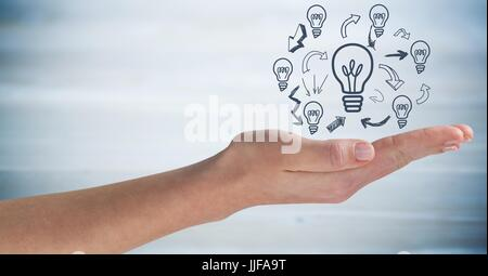 Digital composite of Hand with lightbulb doodles against blurry blue wood panel - Stock Photo