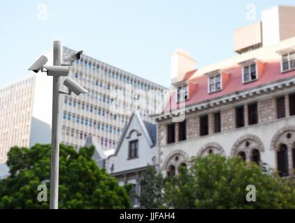 Digital composite of CCTV stick in front of blurred buildings during the day - Stock Photo