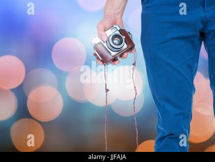 Digital composite of Hand holding camera with sparkling light bokeh background - Stock Photo