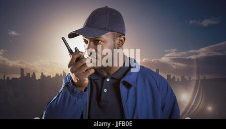 Digital composite of Security guard with walkie talkie against skyline and sunset - Stock Photo