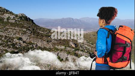Digital composite of Hipster looking at mountains while standing on cliff against sky - Stock Photo