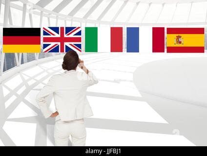 Digital composite of main language flags over businesswoman in the office - Stock Photo