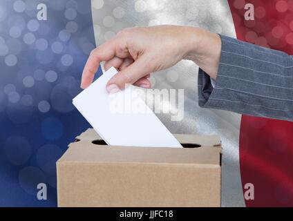 Digital composite of Hand putting France vote in ballot box with sparkling light bokeh background - Stock Photo
