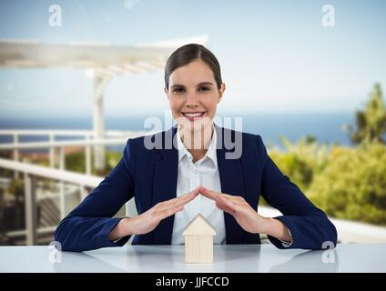 Digital composite of House under woman's protective hands in resort - Stock Photo