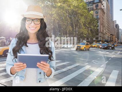 Digital composite of Trendy woman with tablet against sunny street with flares - Stock Photo