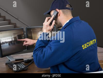 Digital composite of security guard in his office phoning and pointing something in the screen - Stock Photo