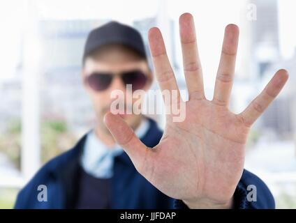 Digital composite of Security man outside with hand stop gesture - Stock Photo