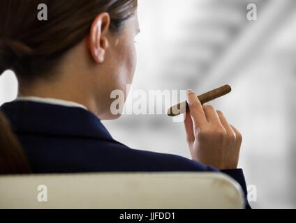 Digital composite of Over shoulder business woman smoking cigar against blurry grey stairs - Stock Photo
