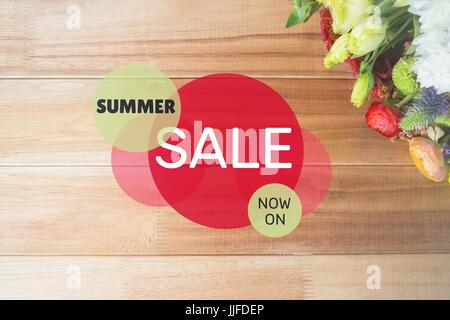 Digital composite of Red and green circular sale graphic on table with flowers - Stock Photo