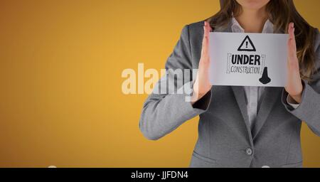 Digital composite of Business woman mid section with card showing grey construction doodle against yellow background - Stock Photo