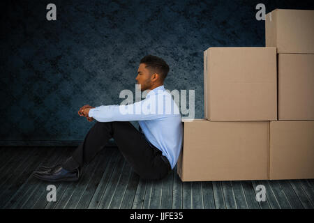 Businessman leaning on cardboard boxes against white background  against dark grimy room - Stock Photo