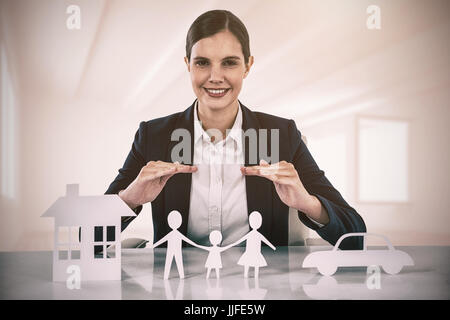 family in white paper with a woman in the background against white room with opened windows - Stock Photo