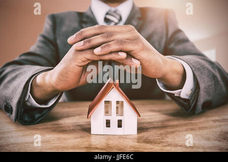 Businessman protecting house model with hands on table against bright room with wall in the middle - Stock Photo