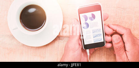 Blue icons on white background against hands holding smartphone next to cup of coffee - Stock Photo