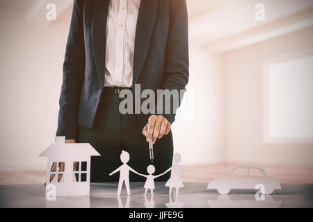 woman drawing a car, a family and a house against white big room with windows - Stock Photo