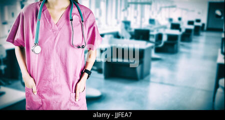 Mid section of nurse with stethoscope against dental clinic - Stock Photo