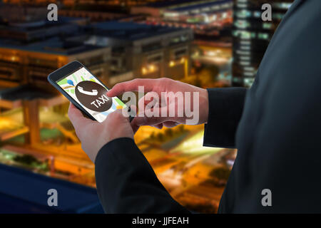 Businessman using smart phone against illuminated road in city at night - Stock Photo