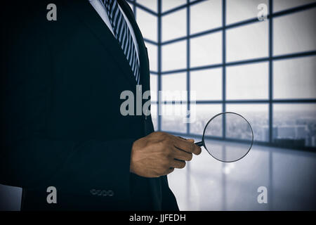 Mid section of businessman holding magnifying glass against room with large window showing city - Stock Photo