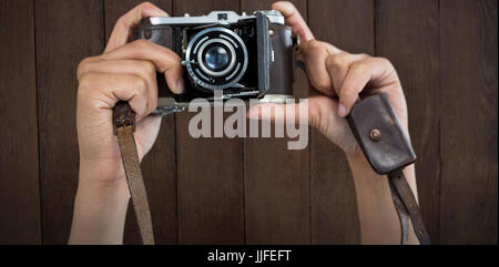 Cropped image of hands holding camera against wood panelling - Stock Photo
