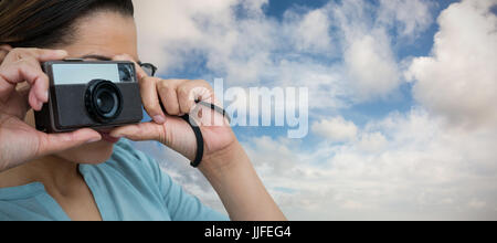 Close up of woman photographing with camera against blue sky with white clouds - Stock Photo
