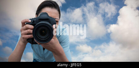 Female photographer photographing through digital camera against blue sky with white clouds - Stock Photo