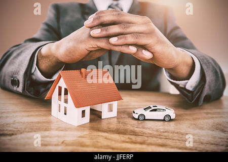 Businessman protecting house model and car with hands on table against bright room with wall in the middle - Stock Photo