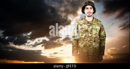 Portrait of confident military soldier standing against blue and orange sky with clouds - Stock Photo