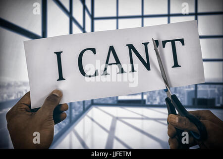 Conceptual image of businessman cutting paper that reads we cant  against room with large windows showing city - Stock Photo