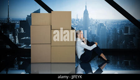 Businesswoman leaning on cardboard boxes against white background against room with large window looking on city - Stock Photo