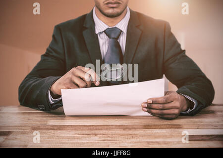 Businessman looking at document through magnifying glass against bright room with two closed doors - Stock Photo