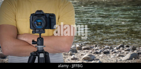 Digital camera on tripod against photographer against rocks at riverbank - Stock Photo