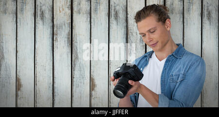 Male photographer looking at digital camera against wood background - Stock Photo