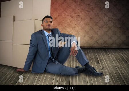 Businessman leaning on cardboard boxes against white background against grimy room - Stock Photo