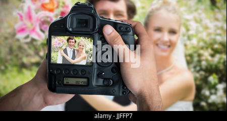 Cropped image of hands holding camera  against portrait of romantic newlywed couple - Stock Photo