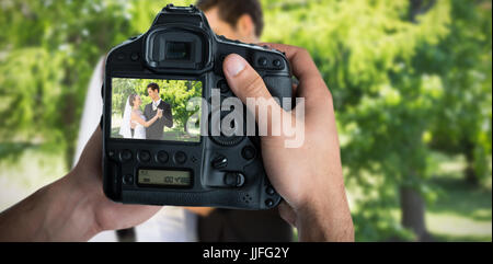 Composite image of cropped image of hands holding camera - Stock Photo