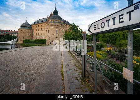 Old medieval castle in Orebro, Sweden, Scandinavia, Europe. Landmark in foreground and blue cloudy sky in background. - Stock Photo
