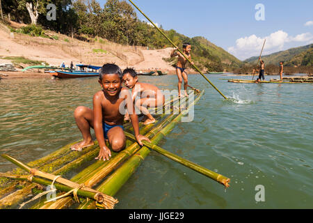 Children play in the Nam Ou River on bamboo rafts at Ban Hat Kham, Laos. The village would be completely inundated - Stock Photo