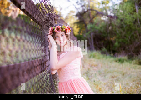 Portrait of a teenage girl leaning against a fence, California, USA