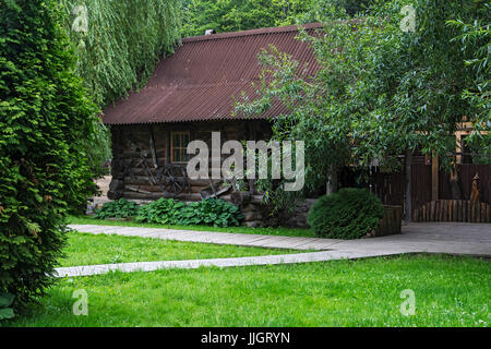 Among the trees is a wooden log house - Stock Photo