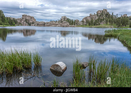 A small log sits in the foreground of the famous Sylvan Lake near Custer, South Dakota. - Stock Photo