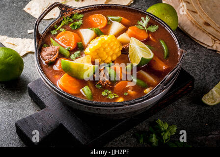 Autumnal vegetable stew. Mexican traditional vegetable soup Mole de olla with meat, potatoes, carrots, beans, corn - Stock Photo