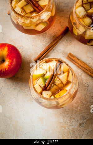 Autumn and winter drinks. Warm apple sangria, apple cider with pieces of fruit, cinnamon, spices, sugar. In glasses, - Stock Photo