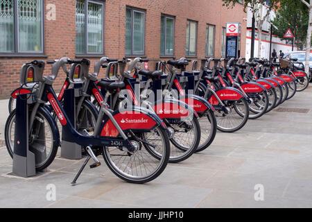 Santander hire bikes at docking station in Kensington, London - Stock Photo