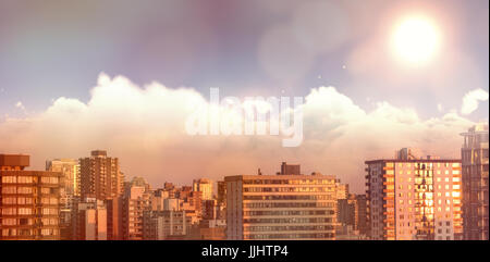 Idyllic view of sun over clouds during sunny day against sunlight falling on buildings during sunset - Stock Photo